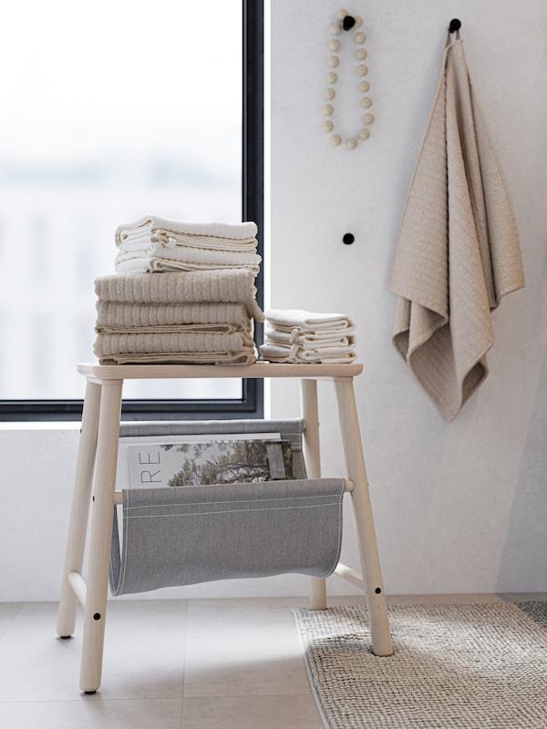 Toallas beixes e brancas ben dobradas enriba dun tallo de madeira. Ganchos negros cunha toalla beixe e un colar de madeira.