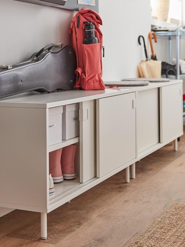 Vit bänk med skjutdörrar visar vita lådor och sneakers inuti. Ovanpå finns ett fiolfodral och röd ryggsäck.