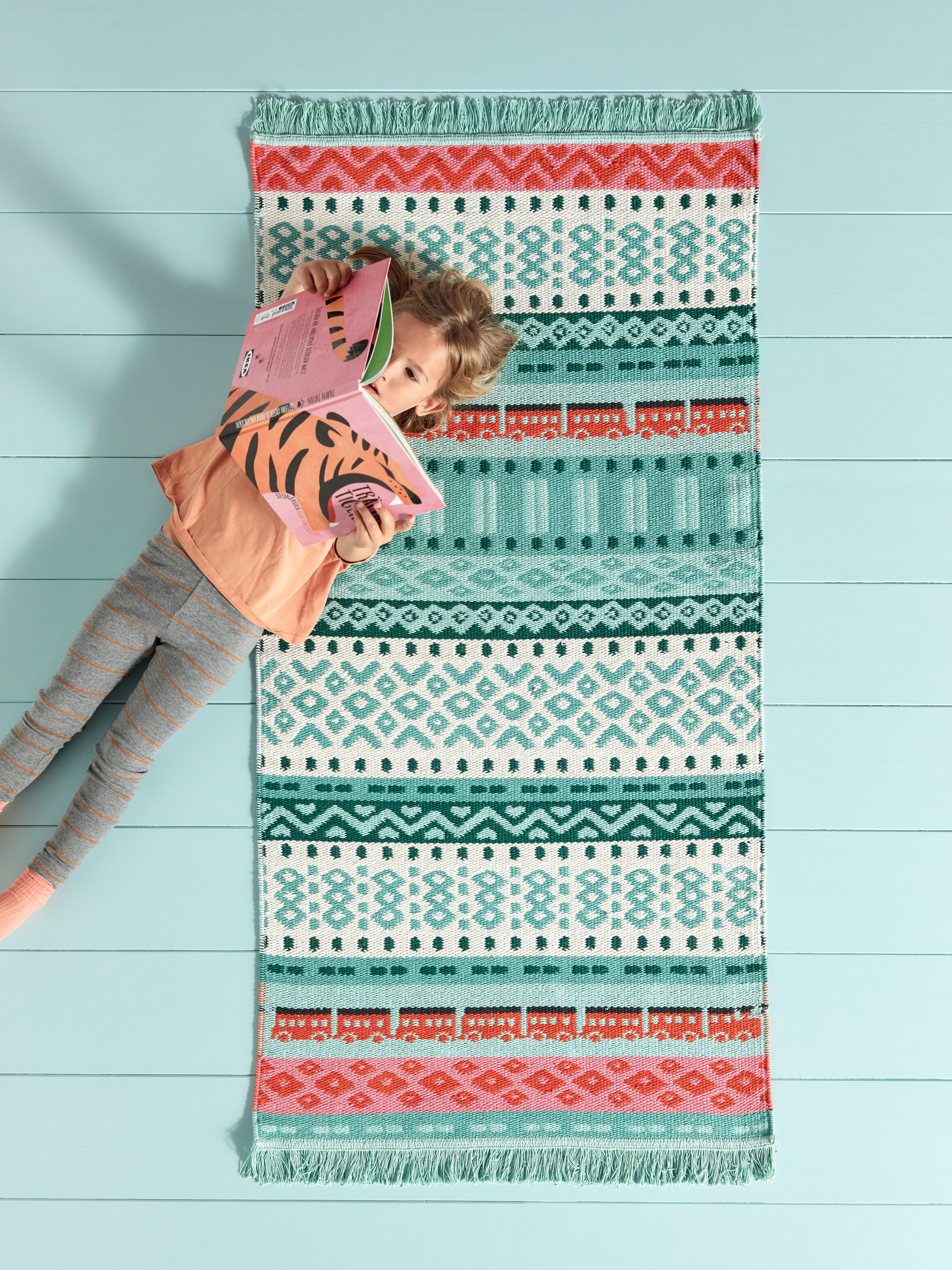 An aerial view of a child reading a book on a multicolor KÄPPHAST flatwoven rug. It has patterns like zigzags and trains.