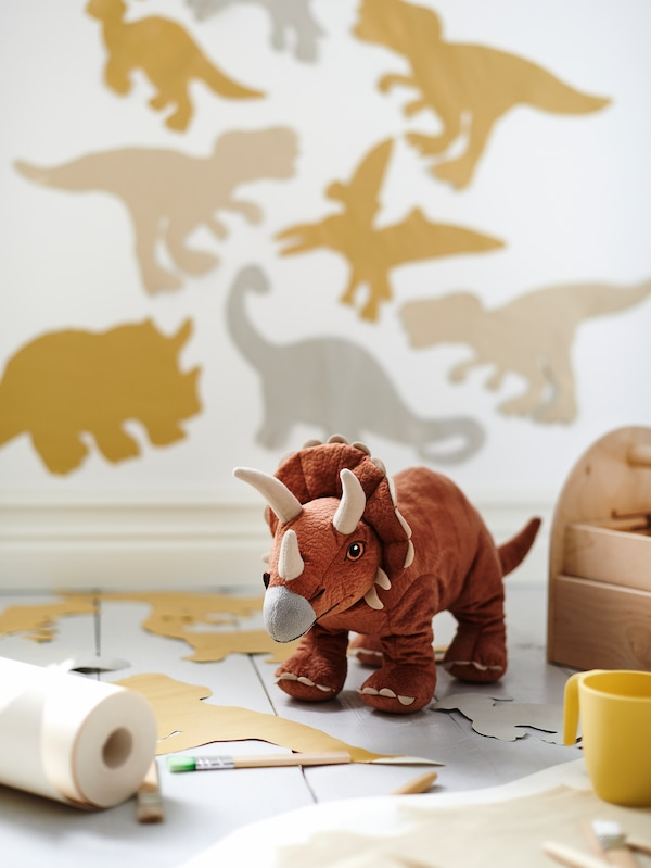 A JÄTTELIK Triceratops dinosaur soft toy on the floor by a yellow cup. Cut-out dinosaurs are on the wall behind.