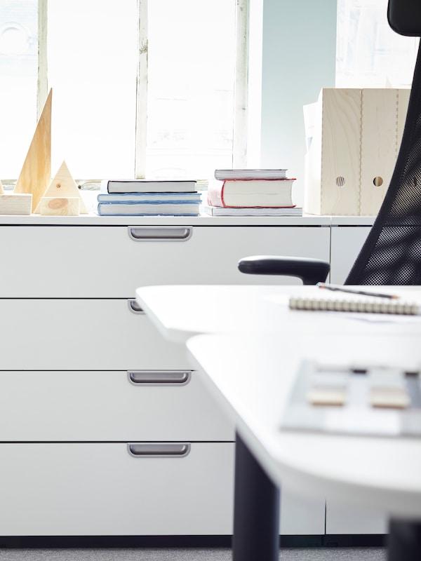 Mobili da ufficio alti bianchi GALANT, con quattro cassetti ciascuno e maniglie color argento, sotto il davanzale di una finestra.