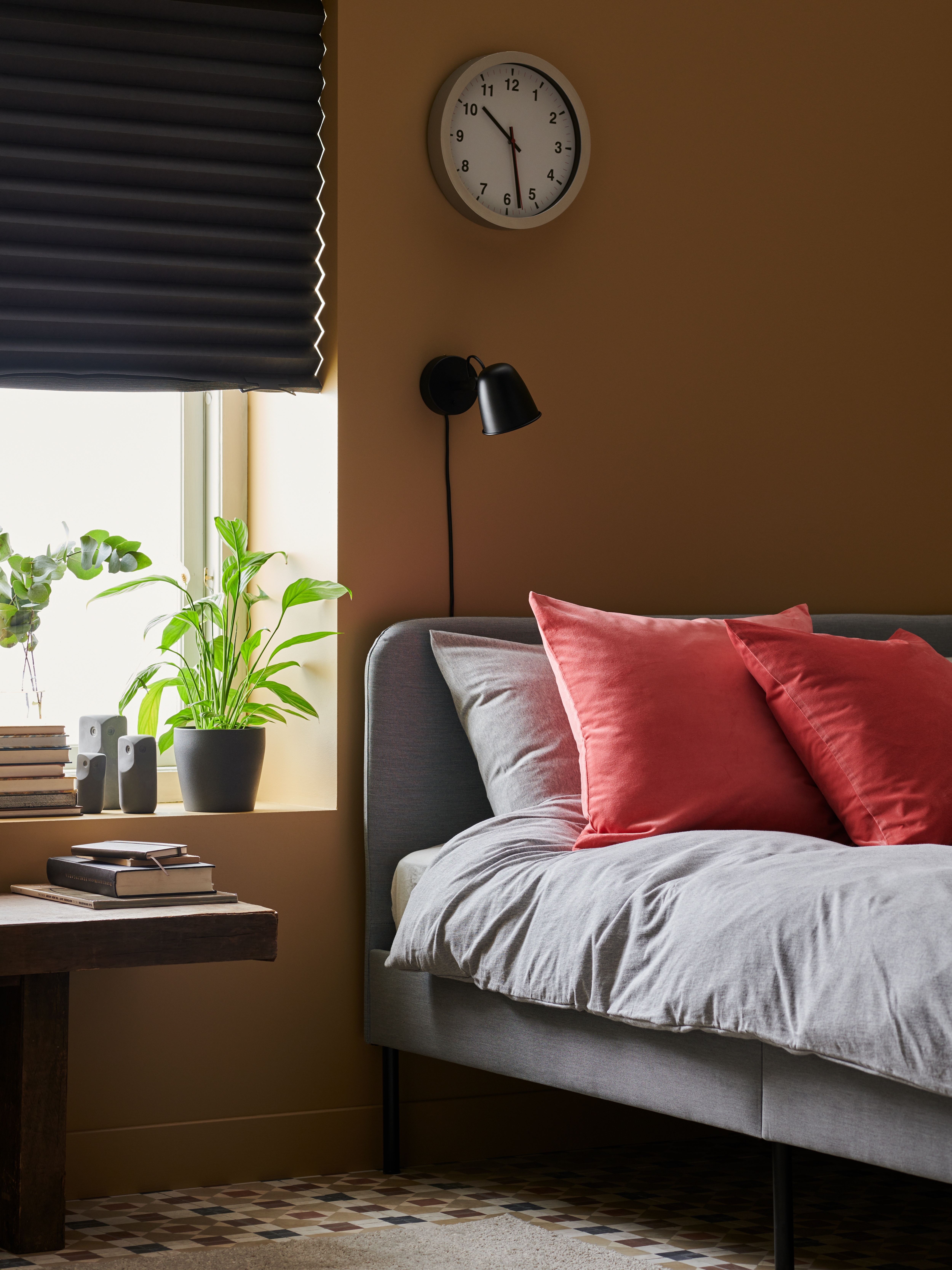 Bed standing by a window fitted with a dark-grey SCHOTTIS blind. On the sill are books and a plant in a PERSILLADE pot.