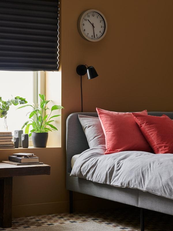 Une chambre à coucher dont le store opaque SCHOTTIS noir est à moitié abaissé, plongeant ainsi la pièce dans la pénombre.