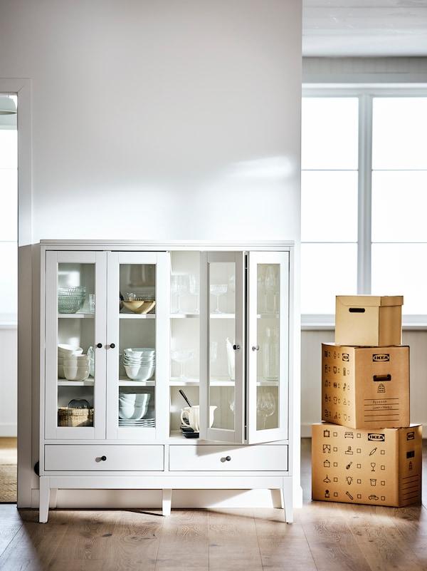 Une pièce dotée de murs blancs et d'un plancher, avec pour seul meuble une vitrine IDANÄS remplie de bols.
