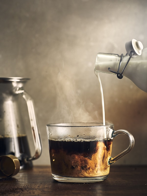 Close-up of milk being poured into coffee in a glass cup on a wooden table and with a coffee pot beside it.