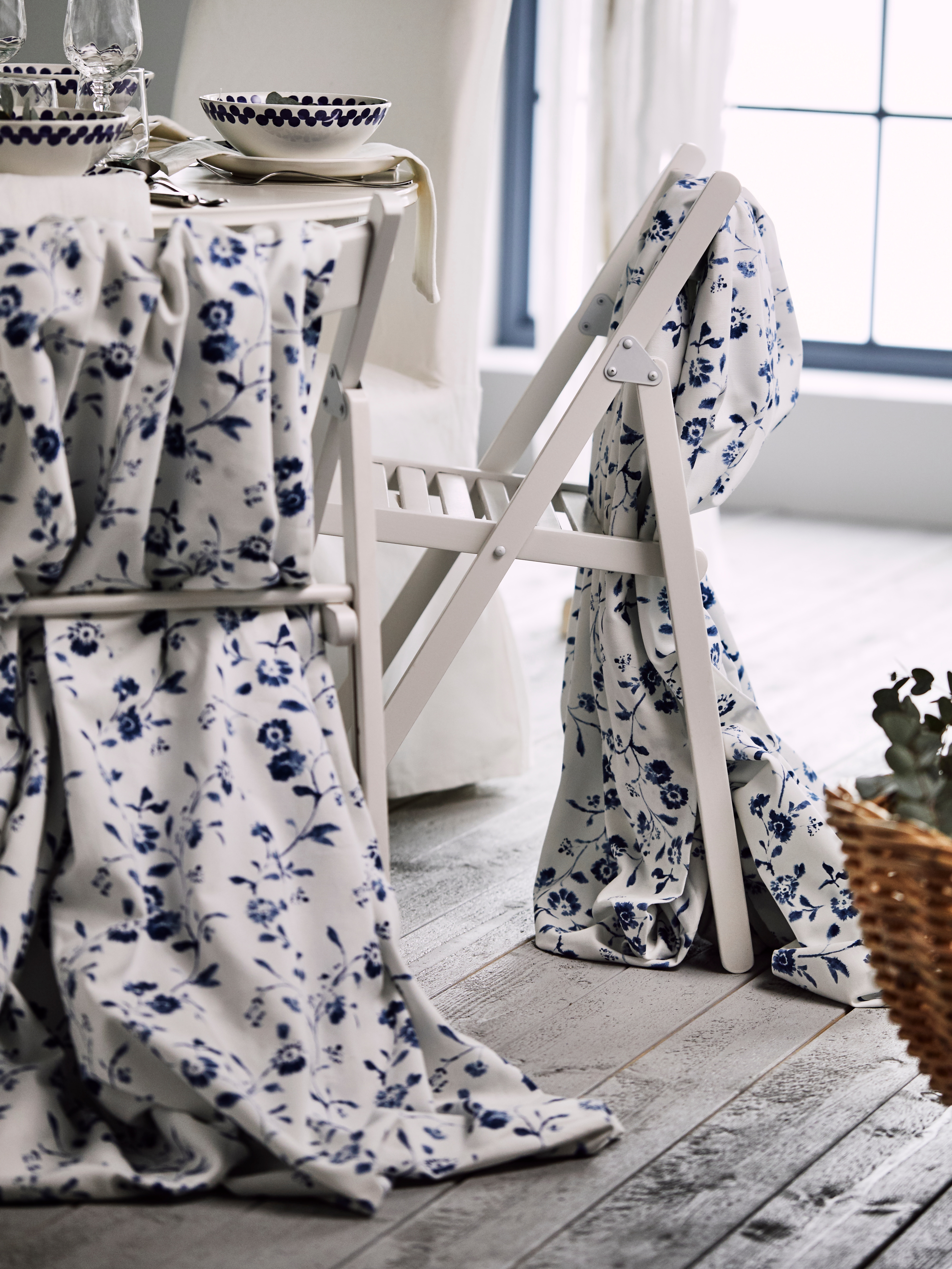 A close-up of white TERJE folding chairs with white-and-blue fabric draped on the backs, by a dining table in a bright room.