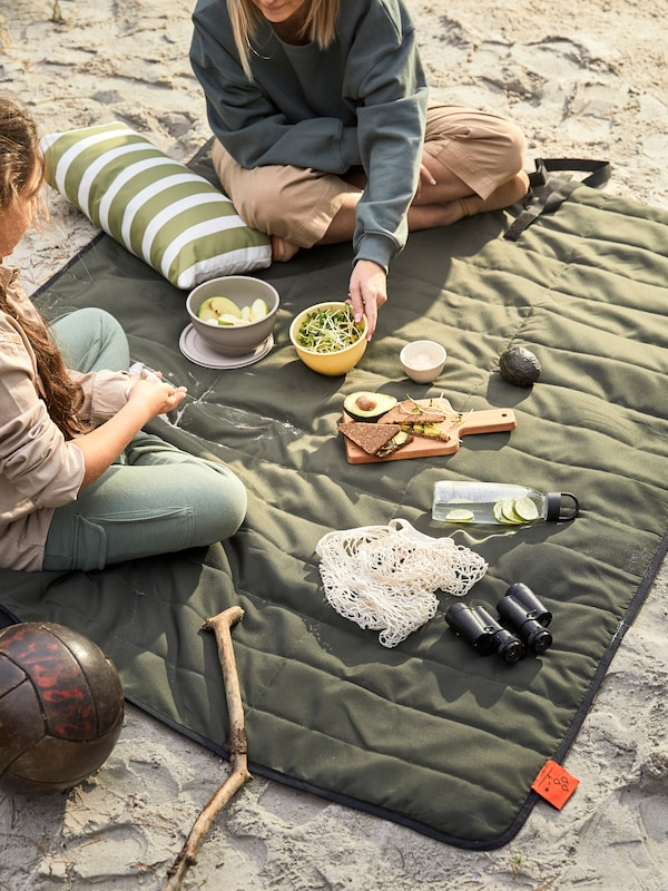 A picnic at a beach with food and other things, including a pair of binoculars, on a FJÄLLMOT picnic blanket.