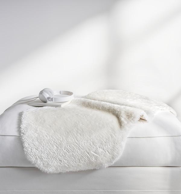 TOFTLUND rug on a white sofa.