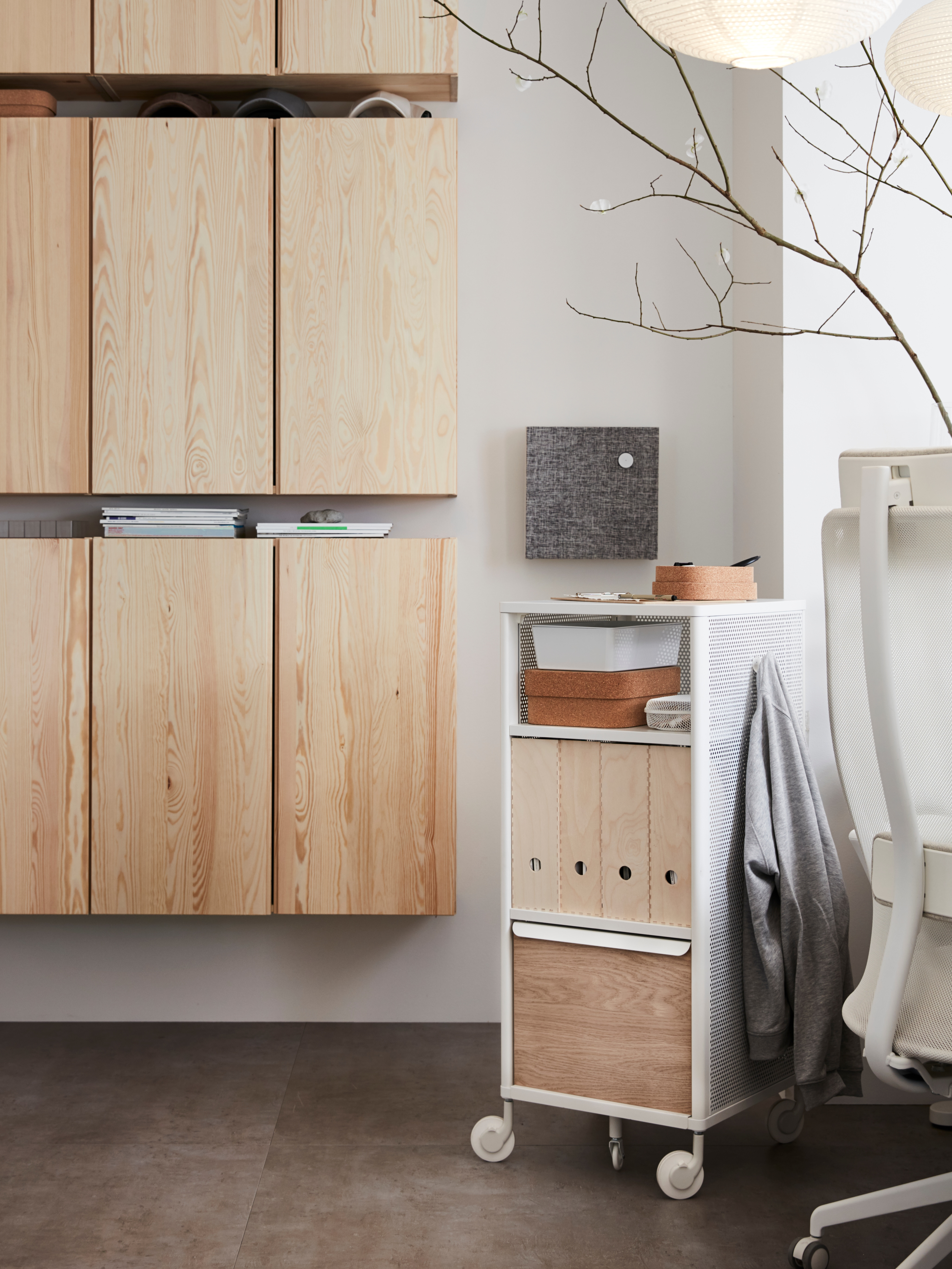A mesh white BEKANT storage unit with smart lock holds wooden magazine files by pine wall cabinets and a white office chair.