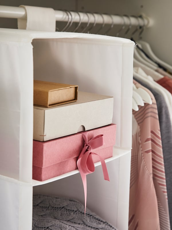 Cardboard storage boxes sit on a shelf in a SKUBB storage with six compartments which hangs from a rail inside a wardrobe.
