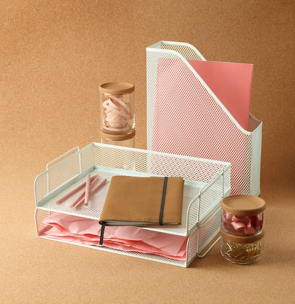 DRÖNJÖNS organizer and file cabinet with several pink paper inside. Beside several colorless bottles with cork lids and a beige notebook.