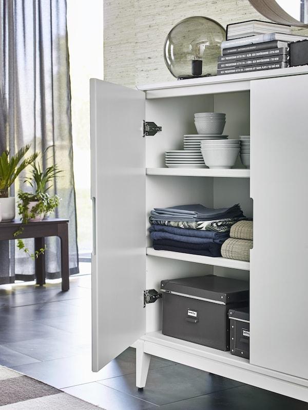 Odprta REGISSÖR bela kredenca, v kateri so zloženi krožniki in sklede, zložene kuhinjske krpe in perilo ter črni zaboji.
