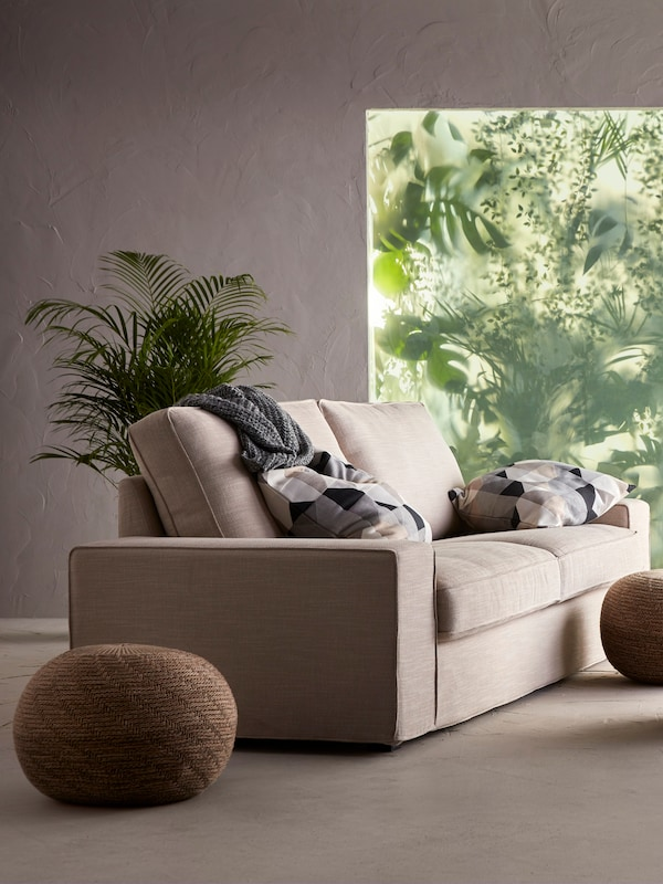 A beige sofa in a room with a large window with plants outside.