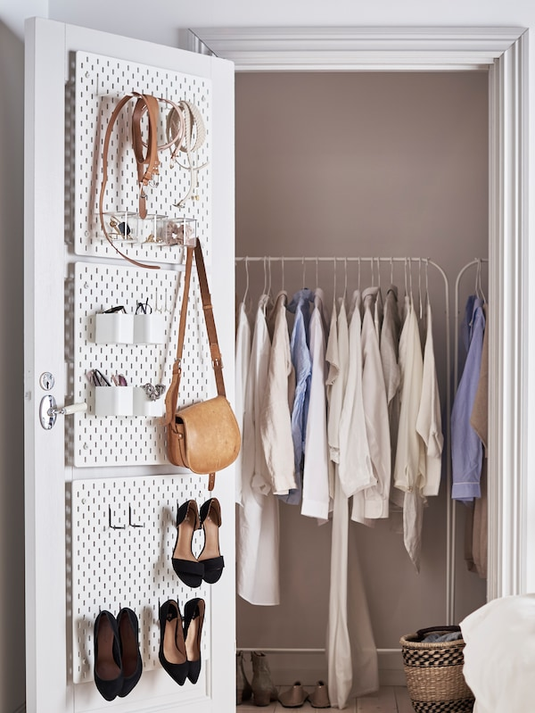 The door of a built-in wardrobe containing MULIG clothes racks and clothes is open. On the back of the door are pegboards.