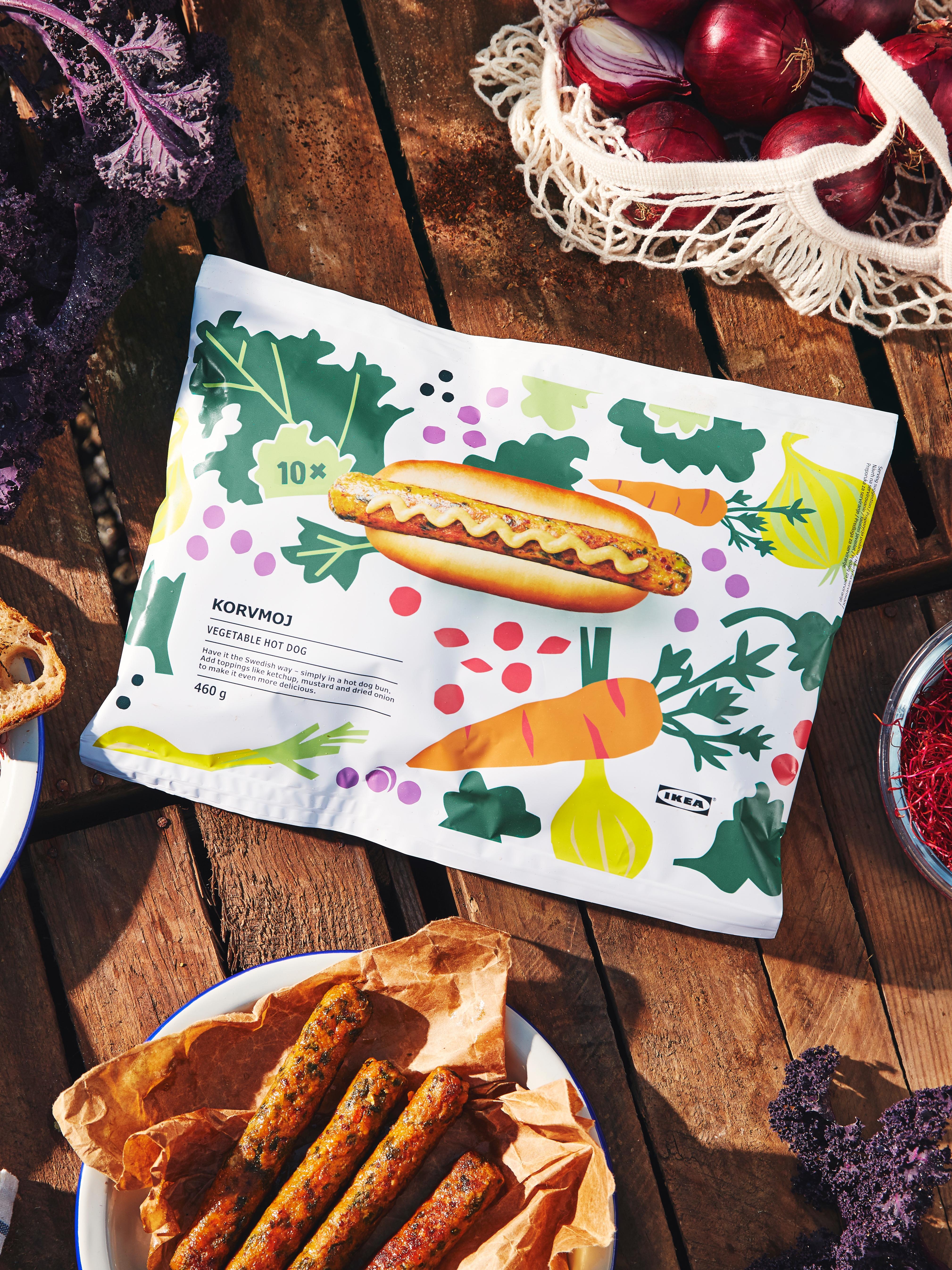 Puna vrećica KORVMOJ hrenovki od povrća na drvenom stolu, uz tanjur hrenovki, vrećicu luka i komadiće kelja.