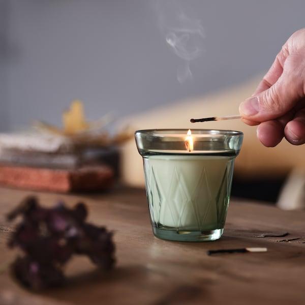 In einem Wohnzimmer zündet eine Hand auf einem Couchtisch eine VÄLDOFT Duftkerze mit einem Streichholz an.