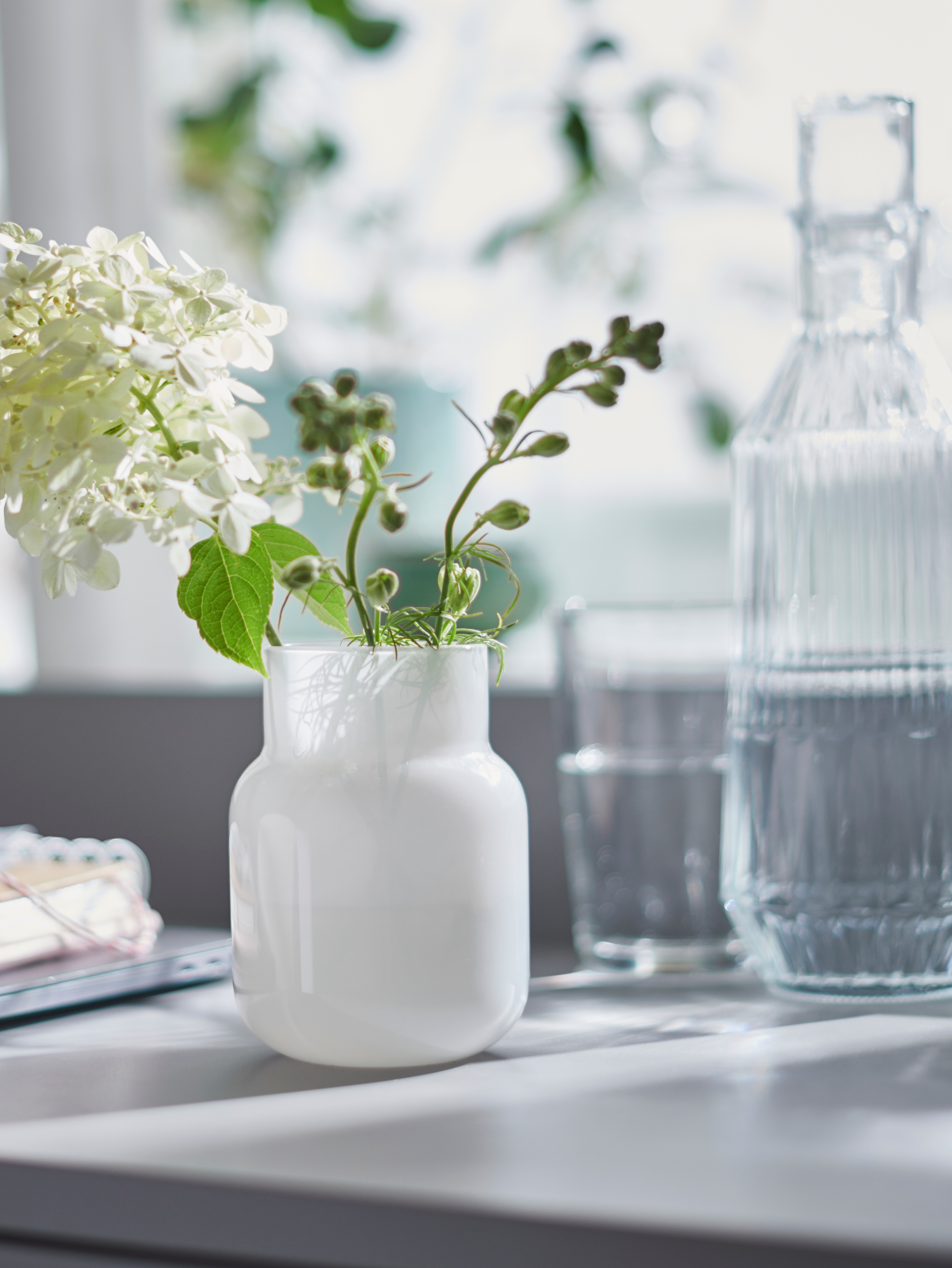 A white FÖRENLIG vase holding a white and green floral arrangement, by a clear glass bottle, in front of a bright window.
