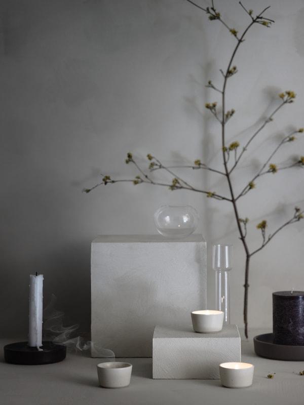 Tre beige ÄROFULL värmeljushållare visas i minimal stillebenmiljö med glas, ljus och gröna växter.