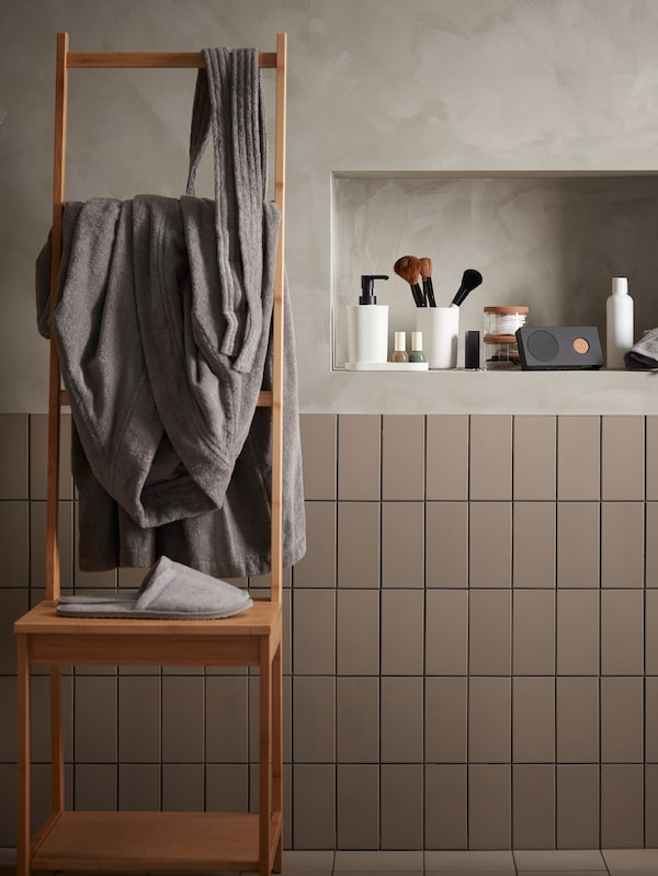 A bathroom with a grey robe hung from a ladder chair, and various toiletries on a shelf.
