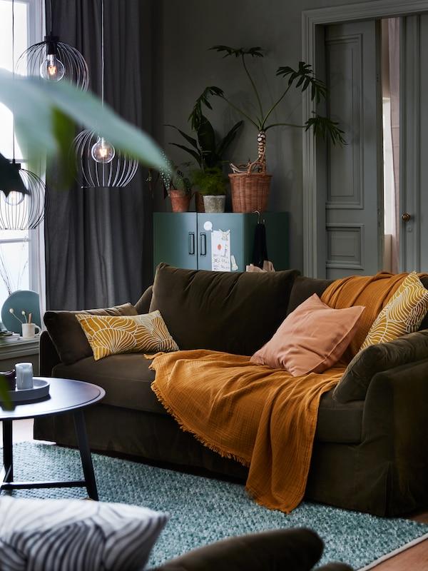 Una habitación de estilo otoñal con cortinas TIBAST, una manta VALLKRASSING sobre un sofá FÄRLÖV y tres lámparas de techo GRINDFALLET.