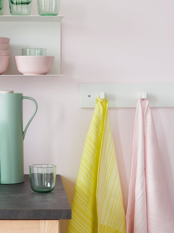 Two TIMVISARE tea towels, one yellow and one pink, hang from hooks next to a kitchen worktop and some shelves.