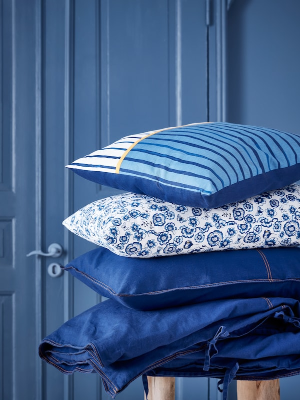SÅNGLÄRKA bed linen and SÅNGLÄRKA cushions with different patterns are piled on top of each other in a blue room.