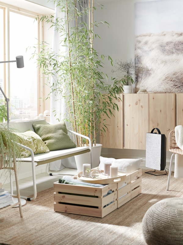 Living room in light tones, with white sofa and green pillows. On the floor is a jute mat and two KNAGGLIG boxes with a tray on top. On the wall is a pine cabinet beside a vase with a plant.