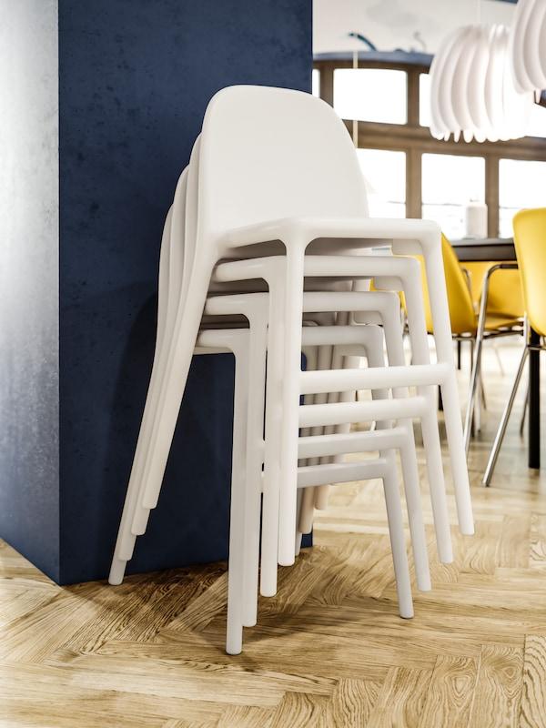 Sedie junior bianche impilate contro una parete blu, pavimento in legno, lampade a sospensione bianche e sedie giallo scuro sullo sfondo.