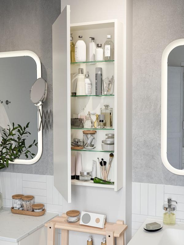 Kabinet tinggi GODMORGON dilekapkan pada dinding di antara dua cermin bilik mandi. Pintu terbuka dan terdapat produk pada para-para.