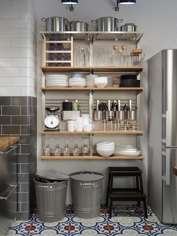Velika zidna kombinacija za odlaganje, s drvenim policama i šinama s posuđem, posudama i priborom.