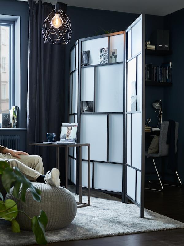 Un salon divisé par un paravent RISÖR, avec un support VITTSJÖ pour ordinateur portable d'un côté, et un espace de travail compact de l'autre.
