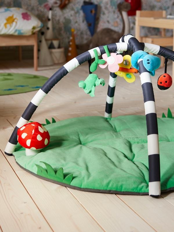 На полу в гостиной стоит детский тренажер КЛАППА, сверху висят божья коровка, бабочка и лягушка, зеленое основание украшено пятнистым грибком.