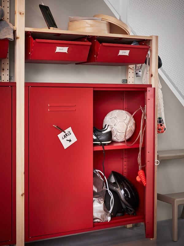 Une étagère IVAR avec des armoires et des tiroirs rouges où sont fixées des notes. Une porte ouverte laisse voir de l'équipement de football et un casque de vélo.