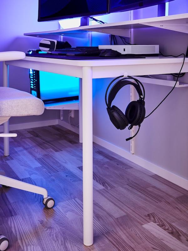 ホワイトのテーブルの横のフックにヘッドホンが掛けてある。その脇にはホワイト/ベージュのオフィスチェア。