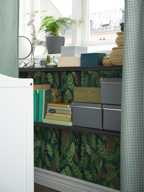 Wall-mounted BERGSHULT/KRUKSHULT shelves under a window with ORDENSFLY curtains hold books, boxes and decorative items.