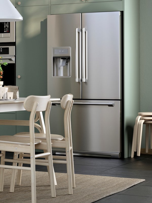 A light-green kitchen with a STJÄRNSTATUS refrigerator in stainless steel. Two pale wooden chairs stand on a rug in front.