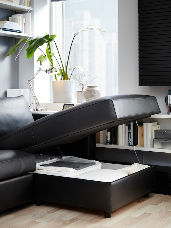 A black leather sofa-bed with chaise longue seat that's open, bedding stored underneath, white shelves and a plant.