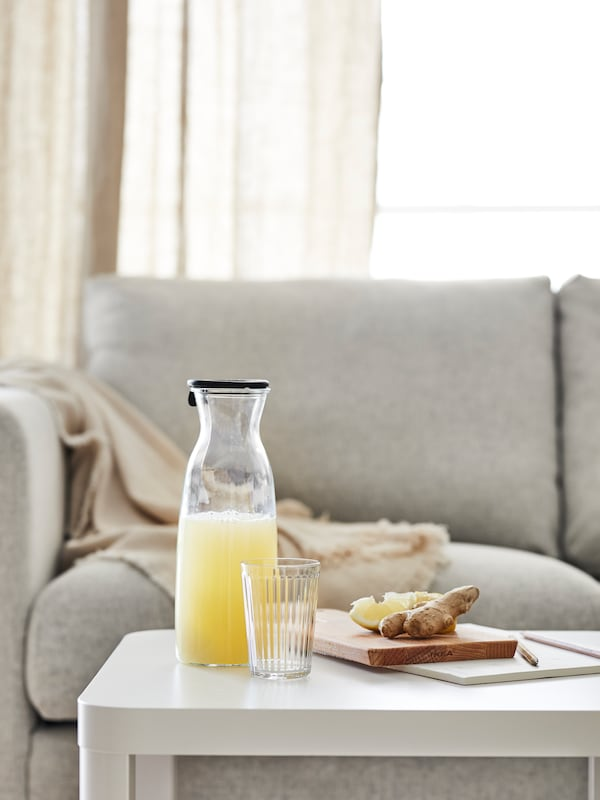 A VIMLE sofa in light gray behind a white side table with a carafe, a clear glass and some snacks.