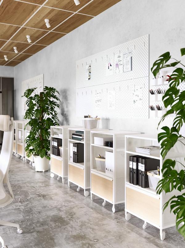 Mobili bianchi con rotelle contenenti portadocumenti neri e libri, allineati lungo una parete bianca con bacheche.
