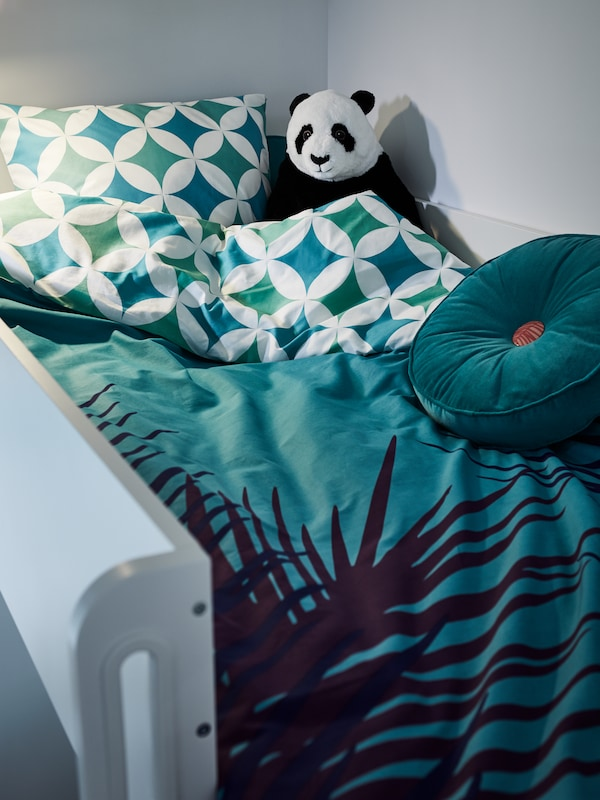 A loft bed with blue and green patterned pillow case and duvet cover, a torquoise round cushion, a panda bear soft toy.