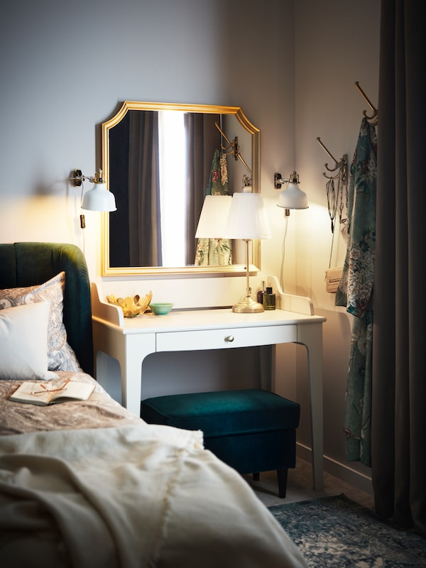 A dark green footstool and a light beige LOMMARP desk with a mirror and two off-white RANARP wall spotlights, beside a bed.