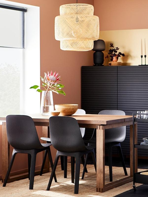 MÖRBYLÅNGA spisebord med svarte ODGER stoler ved et vindu, med et svart skap, et trillebord og ei SINNERLIG taklampe.