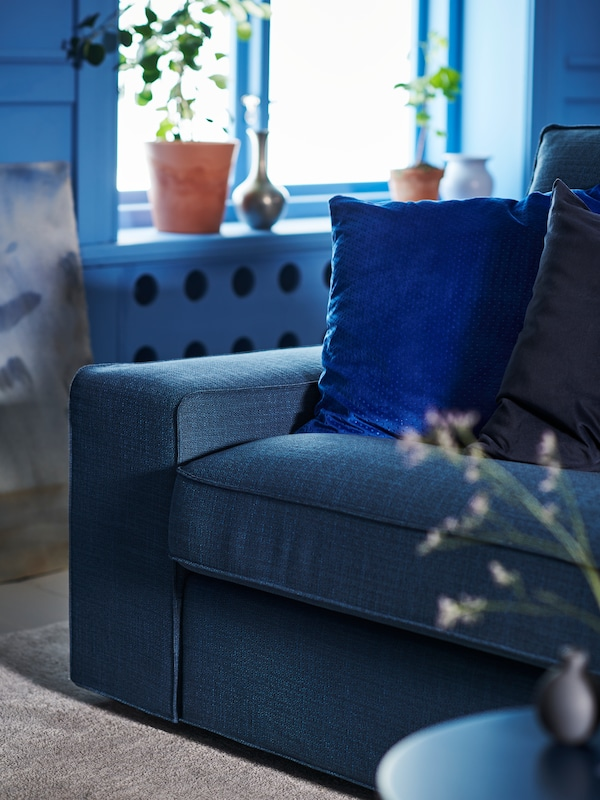 A blue sofa with cushions and a blue wall in the background, with a window, plants and plant pots in the window sill.