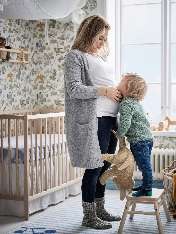 Dijete koje stoji na VILTO stolcu ispred svoje trudne mame koja mu dodiruje lice. Iza njih je SNIGLAR krevetić.