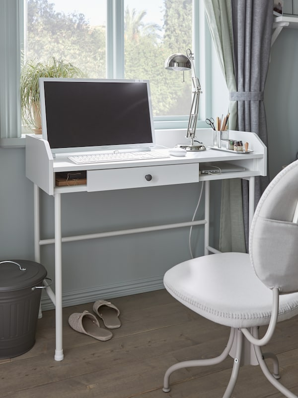 A narrow white desk, a computer screen, keyboard, mouse, metal table lamp, a beige swivel chair and beige slippers.