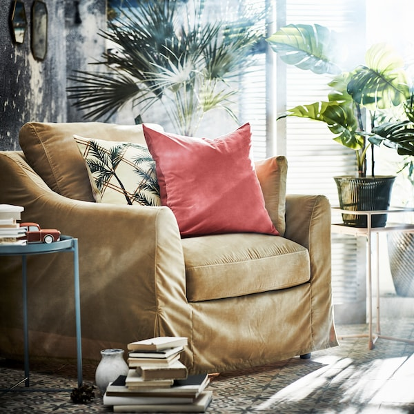 A FÄRLÖV armchair in beige with a light red cushion, and small side tables on both sides, one holding a plant.