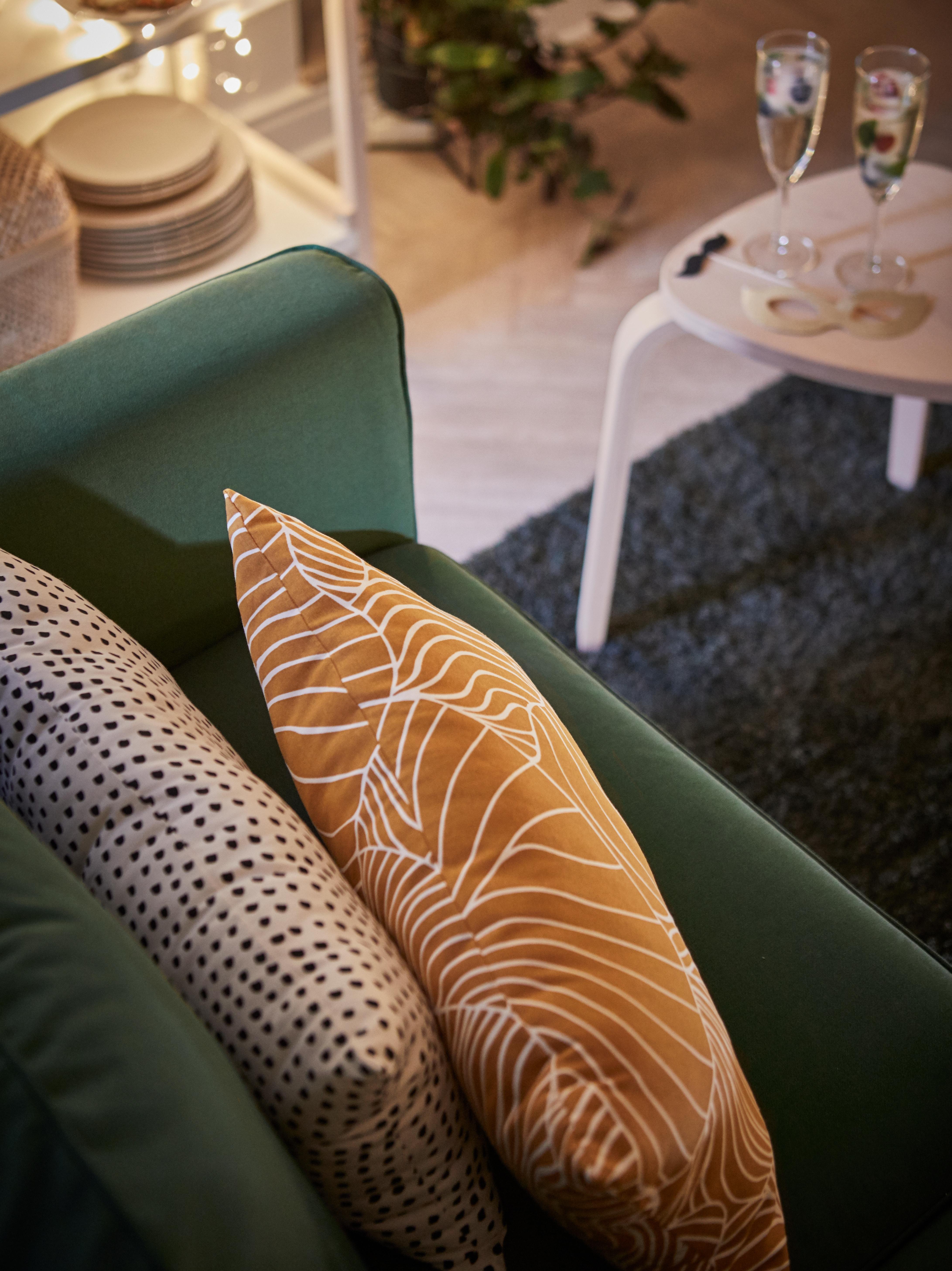 Almofada SVAMPMAL em amarelo escuro num sofá em verde com uma almofada FJÄLLTIMOTEJ em preto e branco.