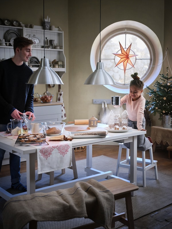 A boy and girl doing festive baking in a traditional-looking kitchen, the table covered in baking utensils and ingredients.