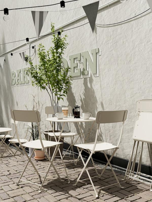 Tavolo su cui viene servito il caffè e tre sedie, tutto in beige. Appoggiate alla parete bianca ci sono delle sedie ripiegate.