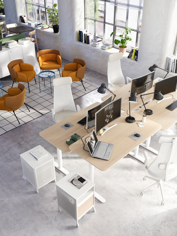 An office space with four white/oak desks with computers and black work lamps on top, next to two white drawer units.